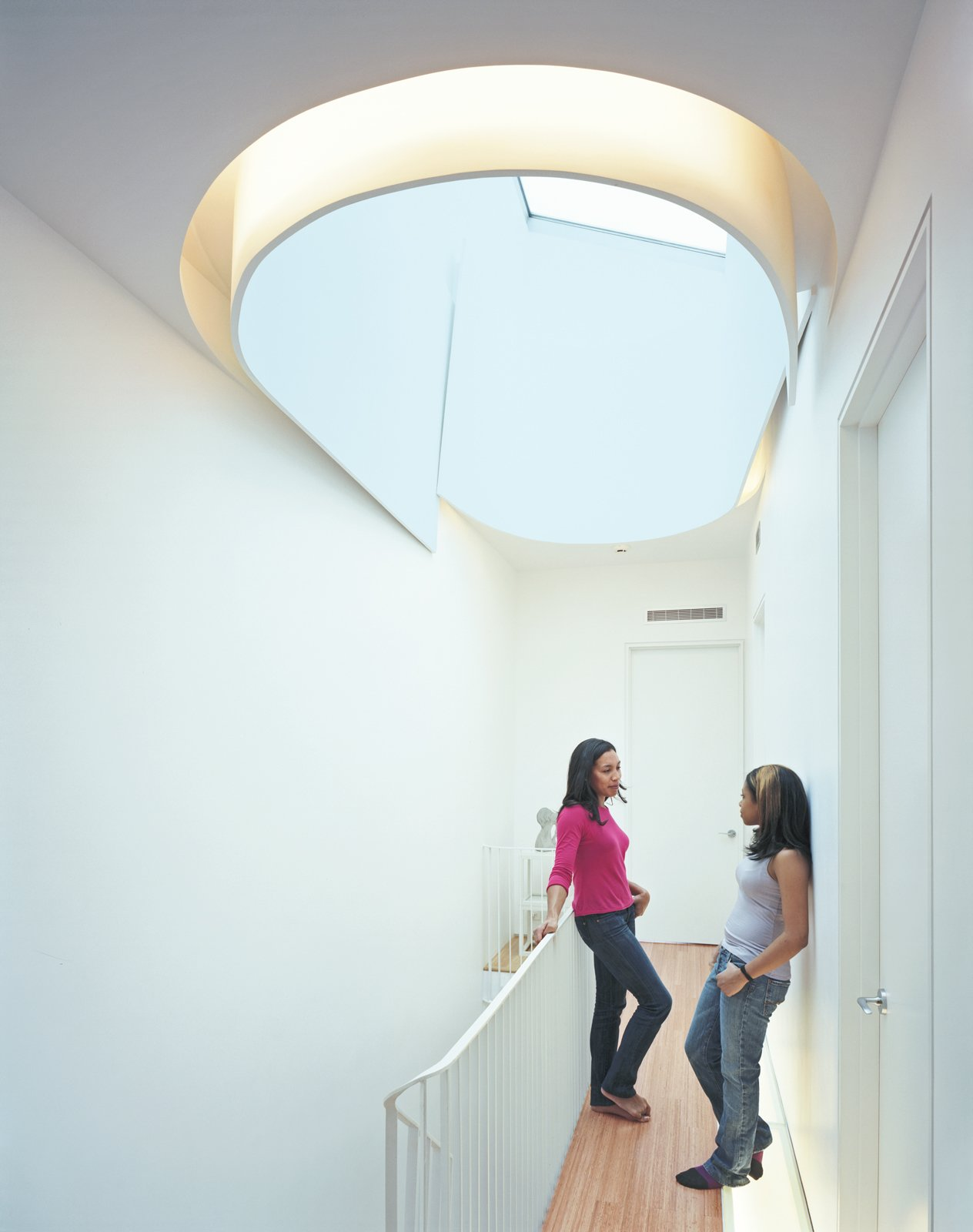 Hallway and Medium Hardwood Floor Keisha Martin and her cousin, Mickeda, chat underneath the house's crowning glory, the oculus, which allows light to spill onto each floor of the house.  Renovating to Maximize Light by Kelsey Keith from Modern Rowhouse Renovation in New York
