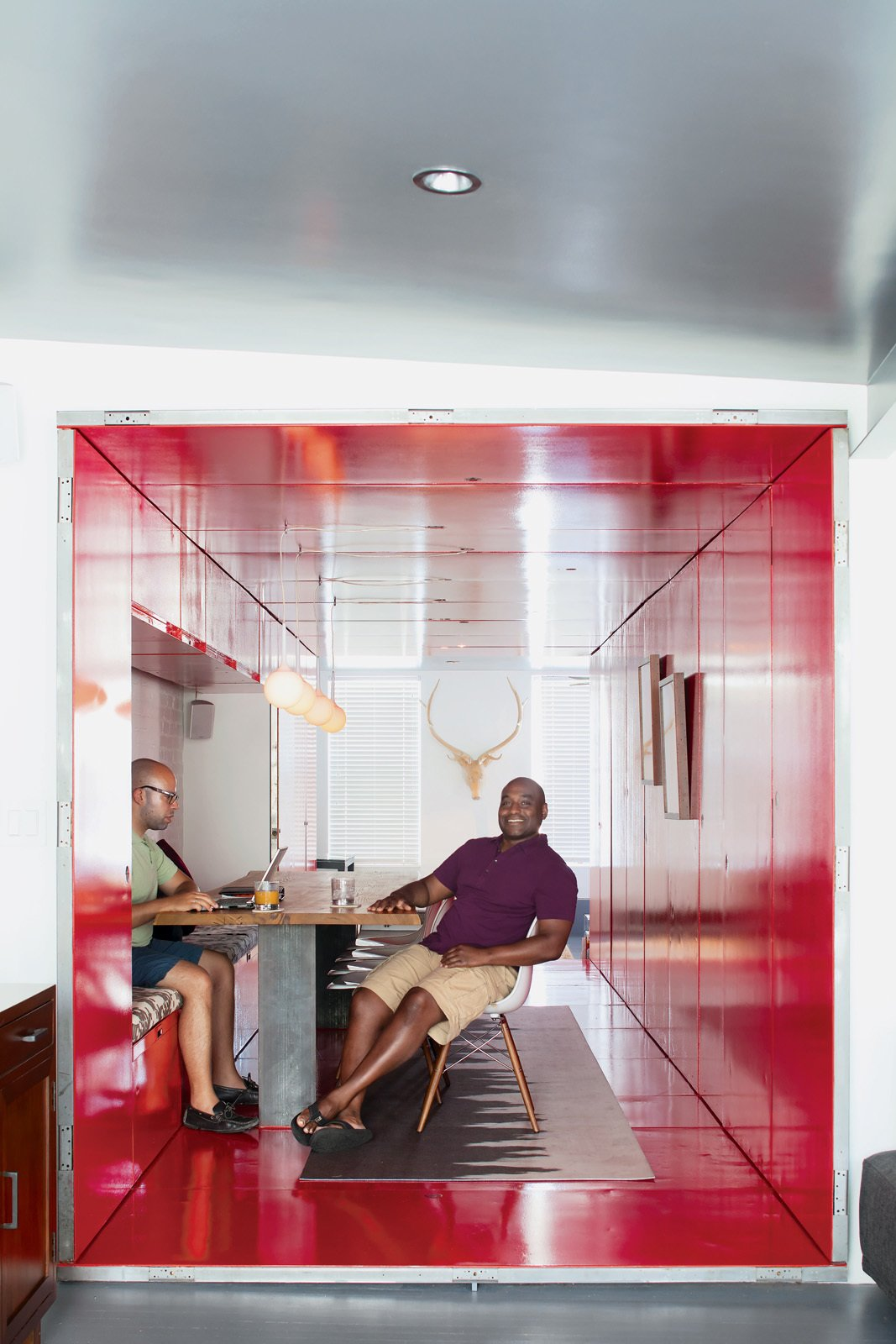 """By inserting a tunnel made from 36 reclaimed commercial doors and tearing down a handful of walls, LOT-EK and contractor Andreas Scholtz brought light into the formerly unused dark hallway in Maurice Russell (right) and Jorge Fontanez's apartment. The glossy Safety Red paint by Benjamin Moore catches the light by day but """"becomes a richer, darker, very relaxing red at night,"""" Fontanez says.  Photo 5 of 12 in The Power of Color and What Each Shade Is Best For from Tunnel Vision"""