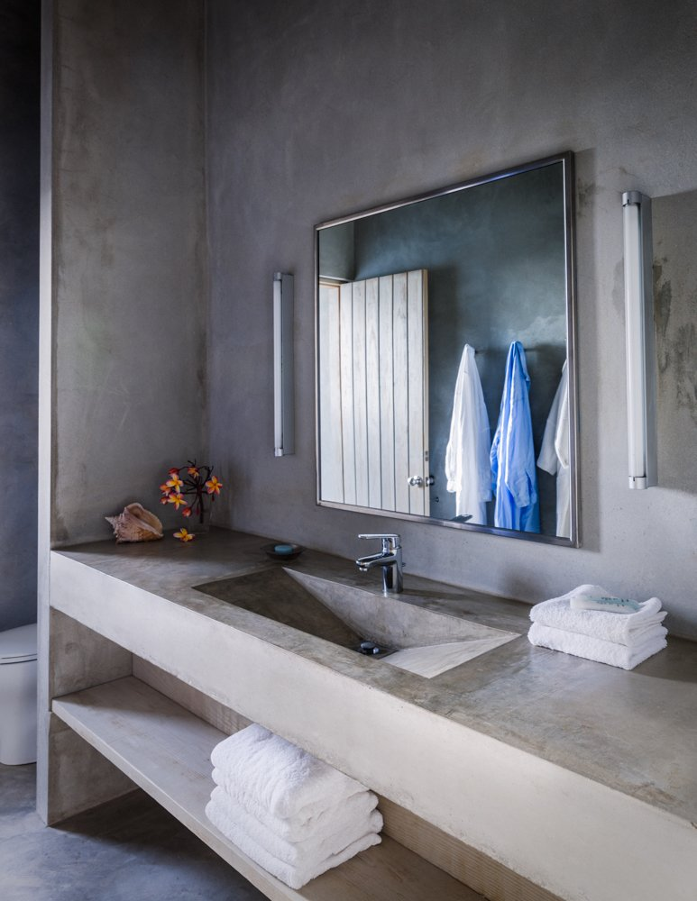 The bathrooms recycle gray water from sinks and showers to help irrigate the surrounding landscape which includes native plants like hibiscus, banana, key lime, and ginger. Amenities include Rusk eco-friendly soaps, Frette towels, and Neeva Gayle night shirts. Photo by Michael Grimm.  Photo 4 of 9 in Modern Concrete Getaway in Paradise