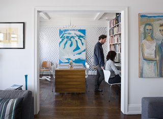 "A second bedroom was converted into a home office/dining room. A Dieter Rams 606 Universal Shelving System (below and opposite) lines the wall. The ""Ziggy Diamond"" wallpaper (behind the surreal Erle Loran painting) comes from Flavor Paper, a New Orleans firm that prints wall coverings to order, and the ingenious folding table is by Swedish designer Bruno Matthson."