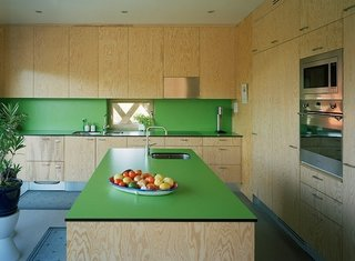 For the Garden House in Viksberg, Sweden, Tham & Videgård Arkitekter plotted the living quarters as a steep triangle with a bright, green kitchen in one corner. The green laminate countertops and backsplash by Abet Laminati contrasts the raw plywood cabinets. The laminate backsplash is on-budget, easy to install, and easy to clean because of the lack of joint lines, where debris and dust can easily collect.