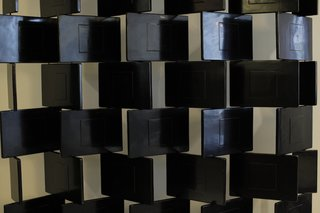 Paravent Briques (Black Brick Screen)   This black lacquered screen exemplified her early furniture and fabrication work. After studying design in London and Paris, she encountered Seizo Sougawara, a Japanese artisan doing restoriation work who helped her master the technique. Initially working out of the bathroom at her apartment ar 21 rue Bonaparte, Gray utilized a time-intensive technique to make lacquered pieces for scores of clients, including a now-lost screen depicting the Milky Way with mother-of-pearl stars.