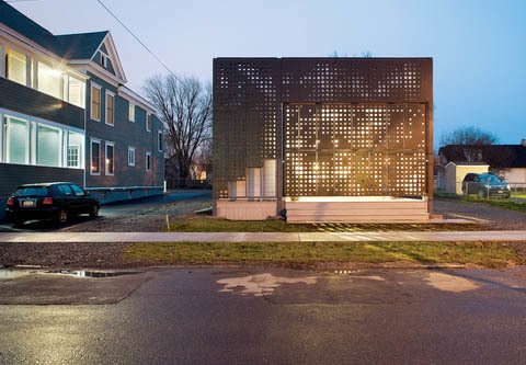 A photograph of dappled sunlight filtering through treetops inspired he perforation pattern in the medium-density overlay plywood solar screen that serves as the exterior for this house in the Near Westside neighborhood of Syracuse, New York. Photo by Richard Barnes.  Uses of Perforated Metal by William Lamb