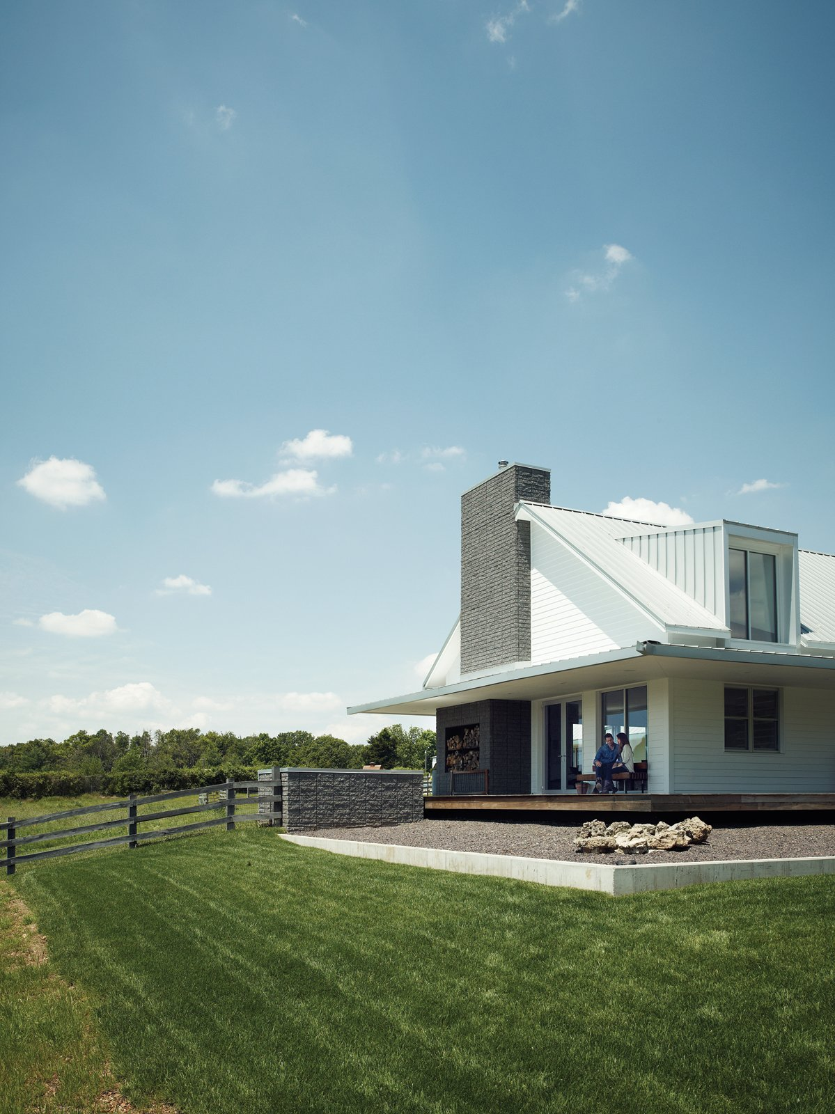 "Grass, Large Patio, Porch, Deck, Wood Patio, Porch, Deck, Exterior, Metal Roof Material, Wood Siding Material, and Farmhouse Building Type ""They were really pushing for a traditional farmhouse,"" explains architect Matthew Hufft, of the Kansas City–based firm Hufft Projects. ""But through the design process, they got more and more excited about modern.""  Fireplace from A Modern Farmhouse Recalls Old-Time Americana"