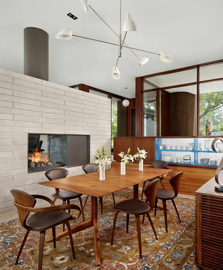 The interior combines modern and more traditional elements, such as this oriental rug. Tagged: Dining Room, Table, Chair, Pendant Lighting, Rug Floor, and Standard Layout Fireplace.  Living space from A Sensitive Modern House in Austin, Texas