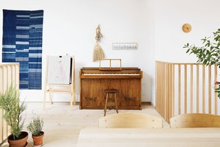 An antique Japanese indigo tapestry hangs by a vintage Danish piano.