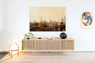 These include the Cesta floor lamp by Miguel Milá and the wall cabinet by Studio Junction in the living room. The photograph hanging above the cabinet is by Joshua Jensen-Nagle. A ceramic dove—a vintage piece by the sculptor Cleo Hartwig—shares space with an antique Zulu beer pot. The painting is by Max Papart.