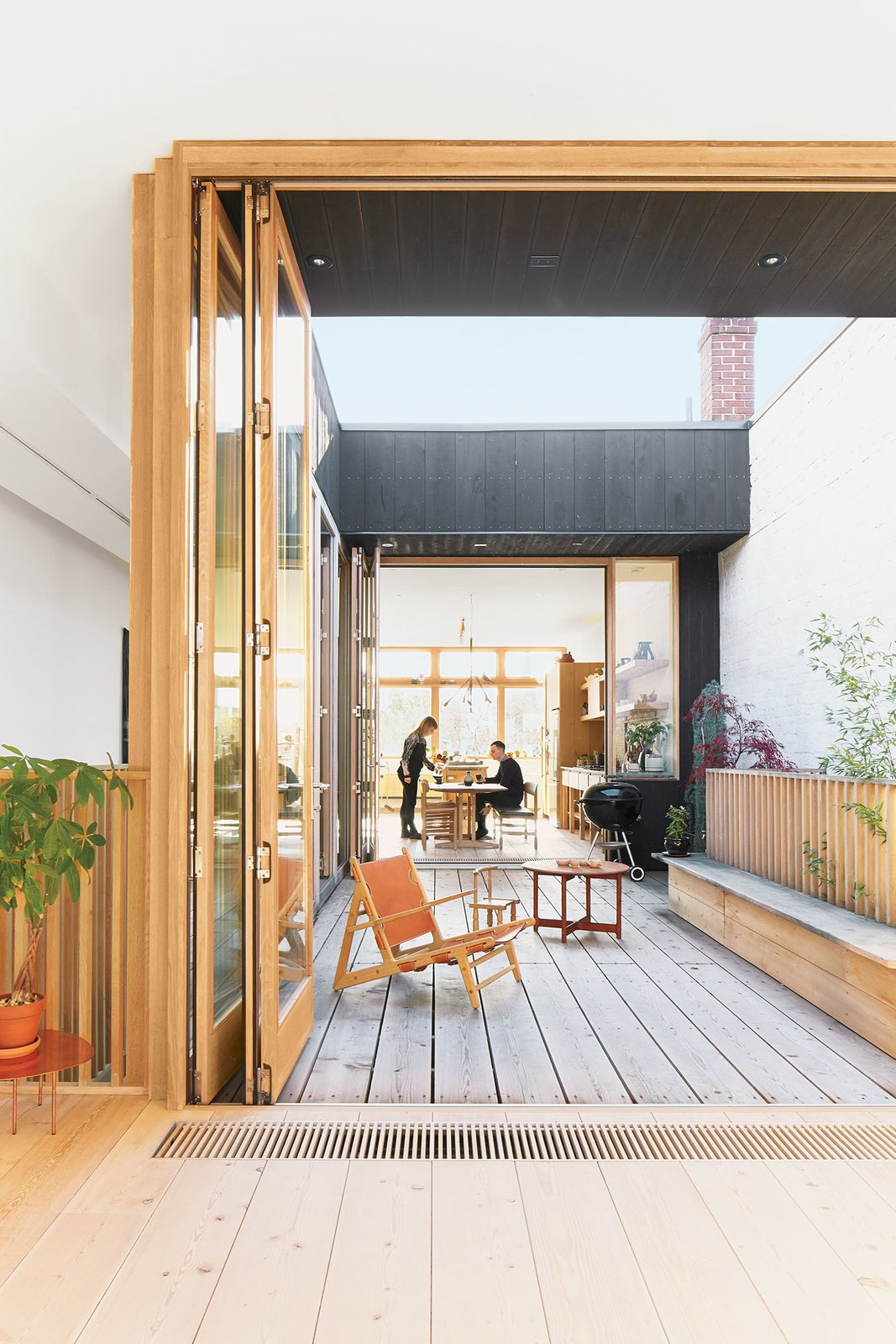 A third-floor courtyard stands in for a backyard and gives Elodie, the couple's two-year-old daughter, a place to play outdoors. A Hunting chair by Børge Mogensen shares the space with a child's chair by   Tomii Takashi and a vintage Danish coffee table. Tagged: Outdoor, Wood Patio, Porch, Deck, and Large Patio, Porch, Deck.  Photo 4 of 10 in These Shop Owners Have a Killer Apartment Right Upstairs