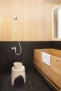A Japanese hinoki bowl and stool from Mjölk sit next to a custom hinoki bathtub by Bartok Design in the tub room.