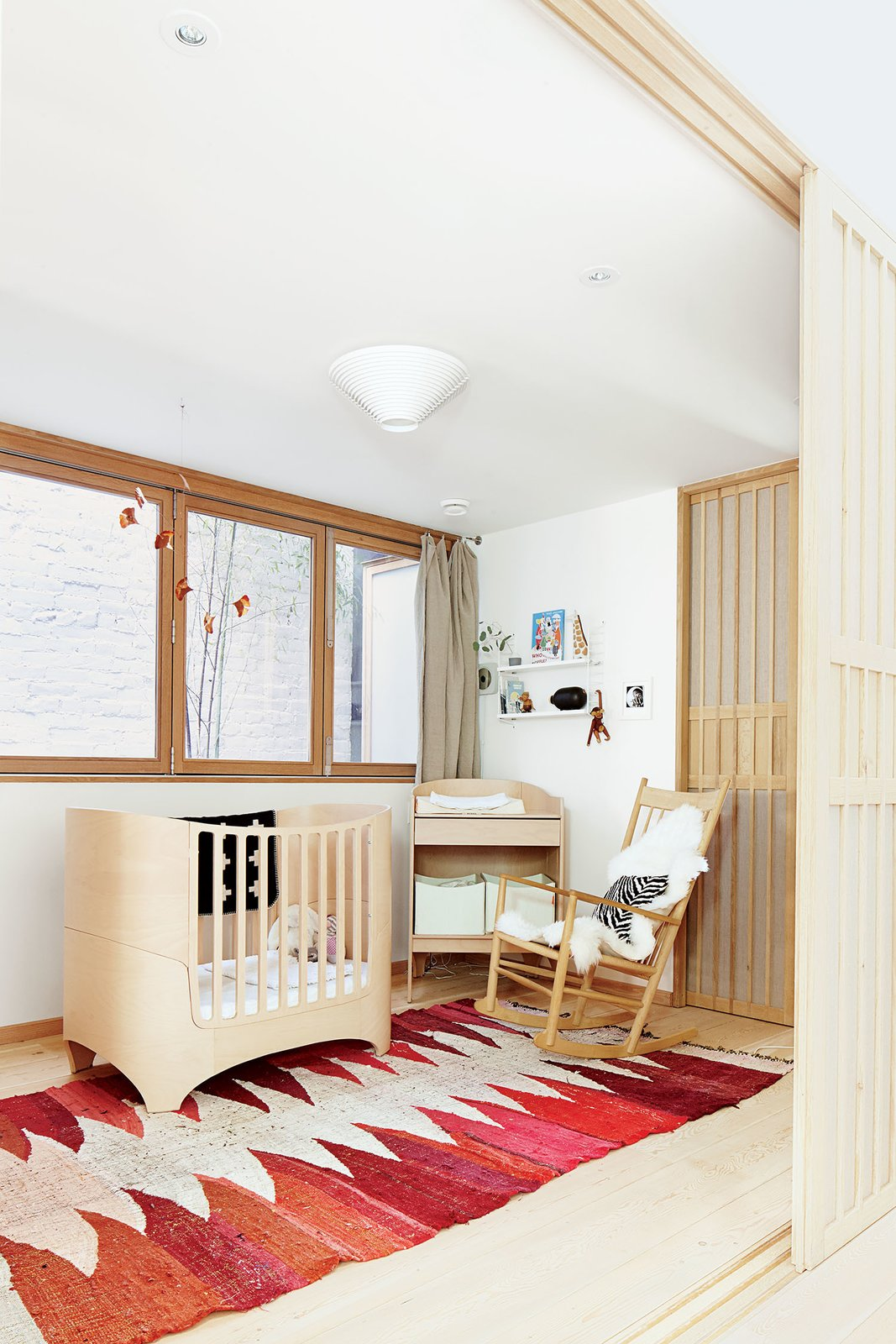 Kids Room, Bed, Bedroom Room Type, Light Hardwood Floor, Toddler Age, Rockers, Neutral Gender, and Rug Floor A copper mobile by JF Jones hangs over a Leander crib and a vintage Moroccan rag rug in the nursery. The rocking chair is by Hans Wegner for Fredericia.  How-To: Patterned Rugs by Dora Vanette from These Shop Owners Have a Killer Apartment Right Upstairs
