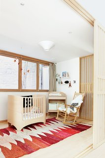 A copper mobile by JF Jones hangs over a Leander crib and a vintage Moroccan rag rug in the nursery. The rocking chair is by Hans Wegner for Fredericia.