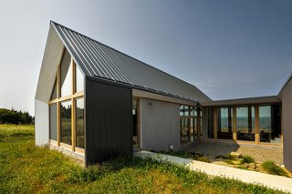 The simple materials and forms represent continuity with traditional Acadian architecture. The retreat is sheathed in metal sheets.