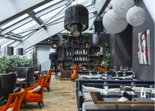 Plush orange chairs pop in this corner of the dining room, pulling the room's steel and blue grey tones into a dialogue, while large, pendulous lamps bring dynamism to the overlapping squares of the shelves lining the room's far wall.
