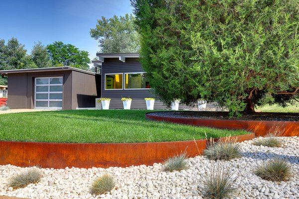 Mature trees define the neighborhood, whose name, Krisana, is a mash-up of the names of the couple whose farm it was originally built on, Kris and Ana. The Cor-Ten steel surrounding the tree and lawn has already developed a patina.
