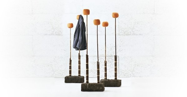 Paola Navone's Black 94 coat rack is black bamboo, stone and orange cotton pompoms. Designed for Gervasoni, the Black 94 is understated and naturally inspired, resembling freshwater reeds.