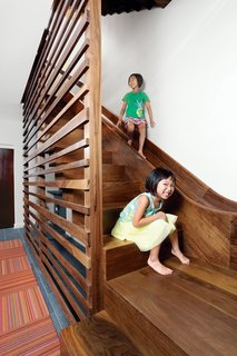 "The walnut staircase and slide in a Chicago town house leads from the main level to the basement. To protect people on the ride down, a ""crash pad"" fashioned from a standard gymnastic mat covers the wall at the slide's base."