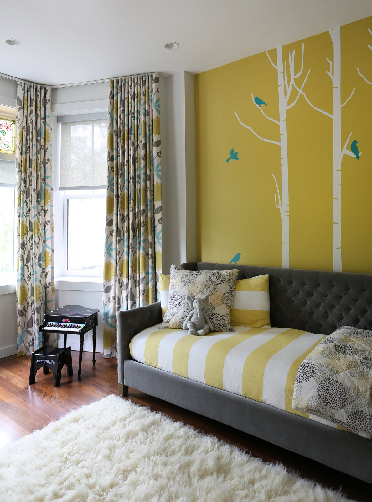 """Fisher characterizes the house as having an """"understated niceness"""" to it. """"The clients wanted everything nice, but not precious,"""" Fisher says. """"A comfortable and functional home that has hints of fun and colorful interjections—just like them."""" Here, a painted wall with decals purchased on Etsy, Restoration Hardware's Devyn Daybed, a Flokati rug from gilt.com, and custom drapery by Workroom Couture Home mix with a toy piano that's been in the family for years.  Lakeview by Diana Budds"""