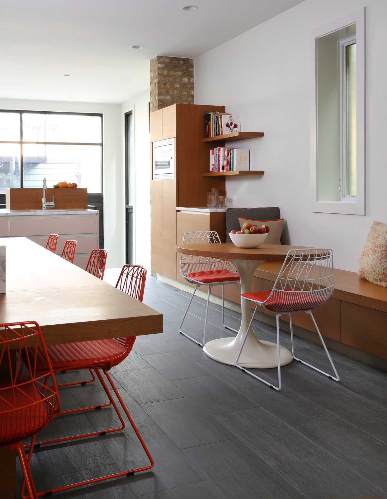 Lucy chairs from Bend and an Eero Saarinen Tulip base outfitted with a custom top offer places to eat and sit in the kitchen. Porcelain tile lines the floor.  Lakeview by Diana Budds