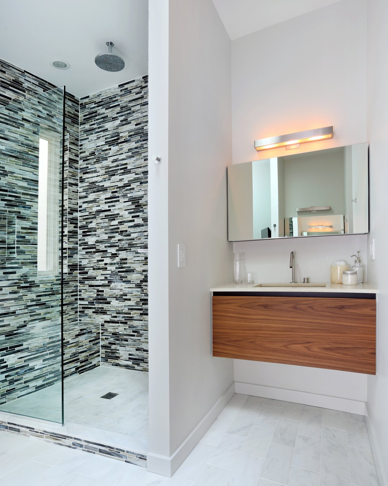 In the master bathroom, glass tile clads the shower and Carrara marble lines the floor. The shower fixtures are Hansgrohe.  Lakeview by Diana Budds