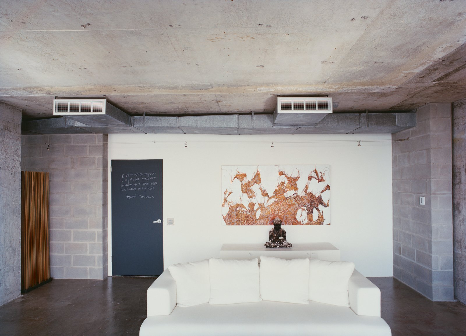 The words of the prophets are written on the chalkboard-paint-coated door to Hill's apartment. A painting by Mark Flood hangs behind a plaster Buddha on a chest from Cassina. The Ligne Roset cotten sofa was bought on sale.  Photo 2 of 11 in Stripped Ease