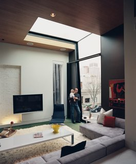 In the living room, a double-height window and a skylight work together to frame a view of the Victorian Gothic church just across the street.