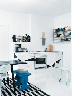 Black and white kitchen cabinets painted with a triangular pattern add a whimsical touch to this funky kitchen.