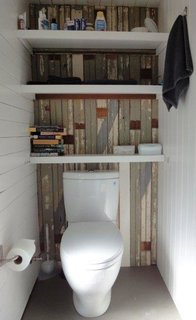 """The bathroom was a """"total scavenger project,"""" says Azevedo. The flooring is a scrap of linoleum left over from another project, and the wall is clad in colorful strips of tongue-and-groove wood salvaged from the basement of the main house. """"But we didn't cheap out: the toilet is a dual-flush Toto Aquia."""" Photo by Susanne Friedrich."""