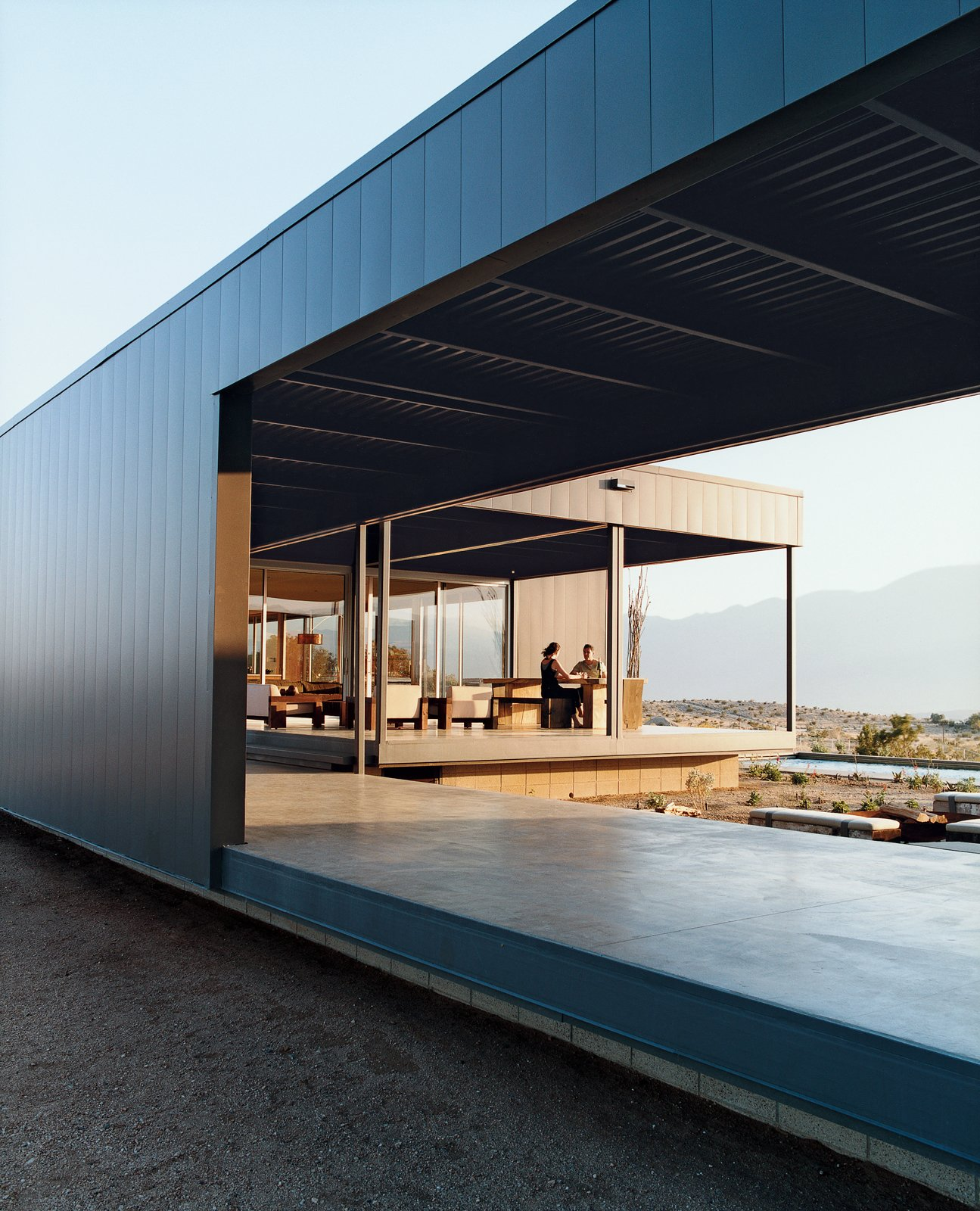 Exterior, House Building Type, Metal Roof Material, Metal Siding Material, and Flat RoofLine Leo Marmol and Alisa Becket enjoy one of their home's many outdoor spaces.  Photo 1 of 9 in Desert Utopia