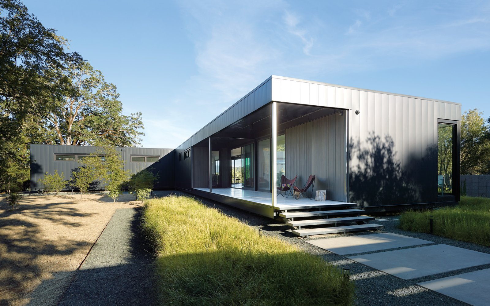 """Outdoor and Front Yard When Abbie and Bill Burton hired Marmol Radziner to design their prefab weekend home, their two requests were """"simple-simple, replaceable materials,"""" says Abbie—such as concrete floors (poured offsite in Marmol Radziner's factory) and metal panel siding—and """"the ability to be indoors or outdoors with ease."""" Deep overhangs provide shade and protection from rain, so the Burtons can leave their doors open year-round and hang out on their 70-foot-long deck even in inclement weather. They visit the house once a month, usually for a week at a time, with Vinnie and Stella, their rescue Bernese Mountain dogs. Their two adult children occasionally join them. The couple hopes to one day retire here.  Exteriors by Matthew Keeshin from A Simple Plan"""
