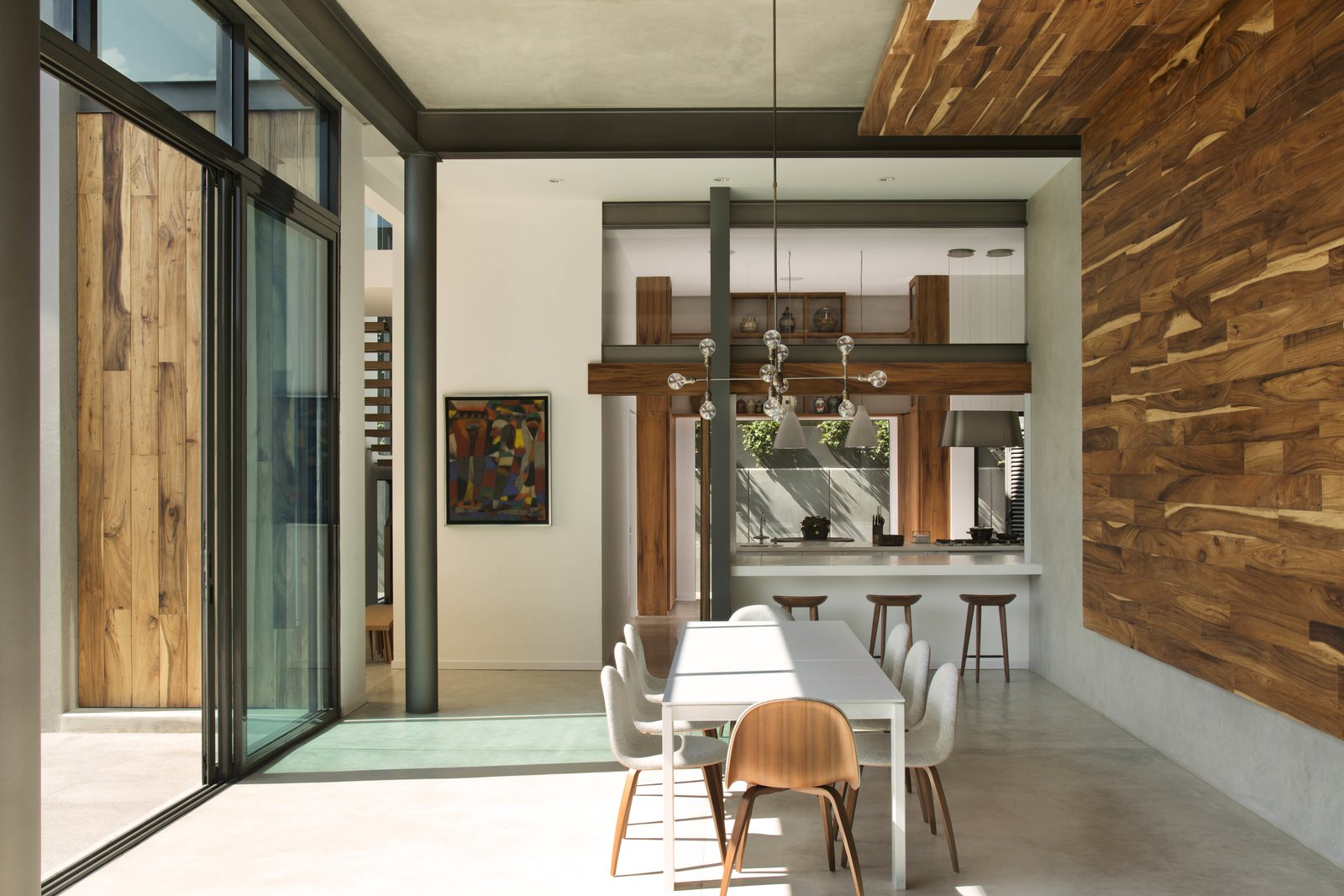 The dining room features Design Within Reach chairs, a Ligne Roset table, and a chandelier from Apparatus.  Modern Open-Plan Retreat in Mexico City by Monique Valeris from Eight Daring Designs in Mexico City