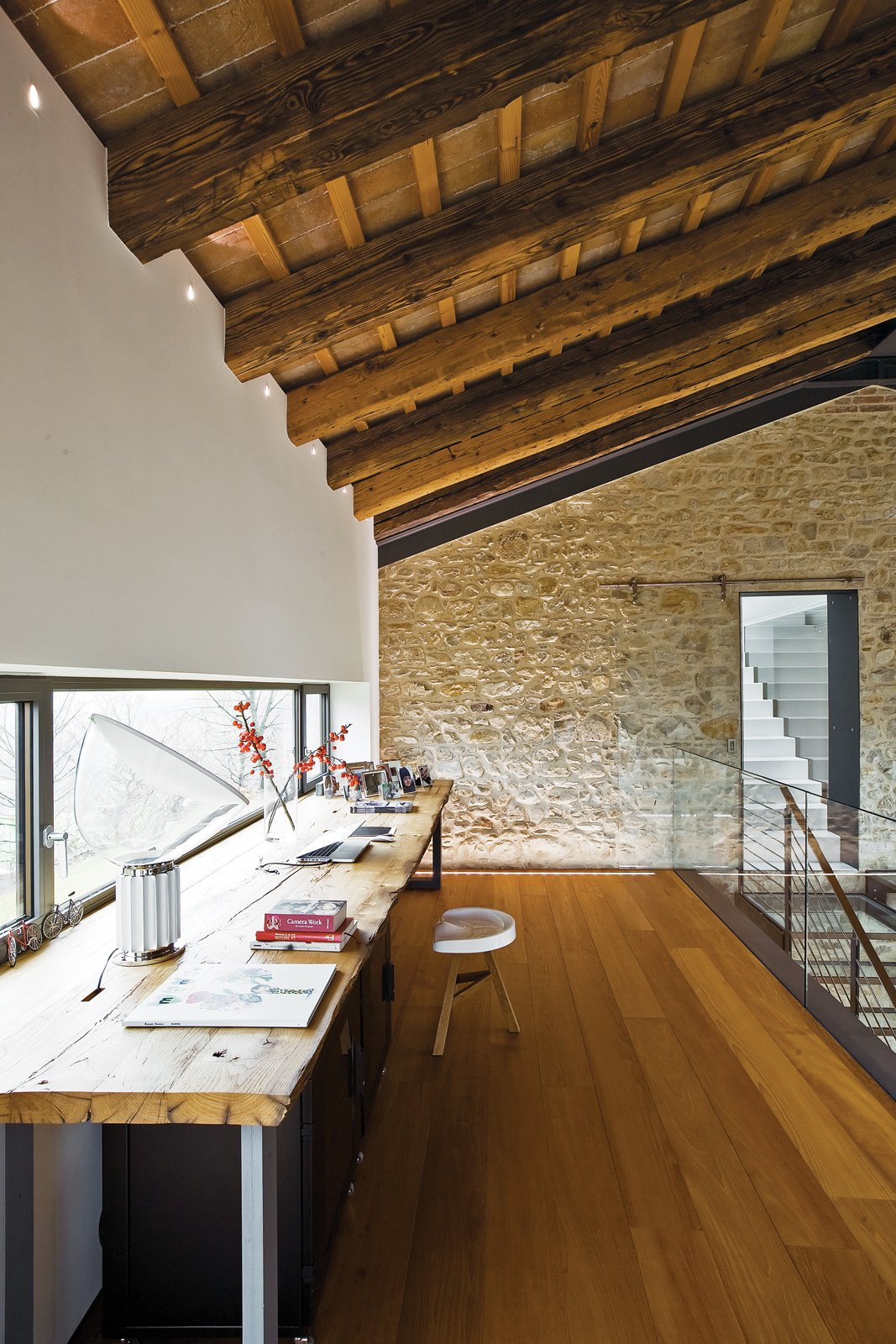 """Office, Chair, and Medium Hardwood Floor """"At first we thought we might not need that much space, but then we started thinking long term. We look at this house as the home of our lifetime."""" —Guido Chiavelli  Photos from A Renovated Farmhouse in Northern Italy"""