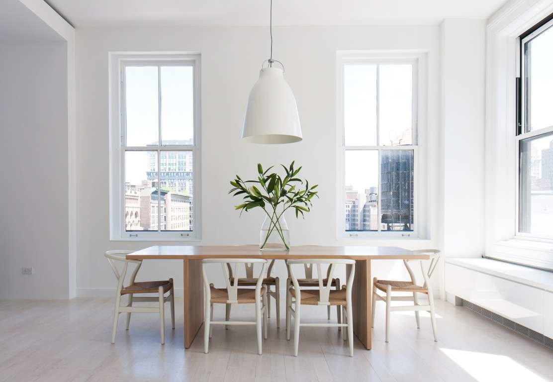 Resolution 4: Architecture designed a Union Square duplex for an expat couple with two children. Hans Wegner Wishbone chairs are arranged around a wooden dining table in one sunny corner of the apartment.  In the Home