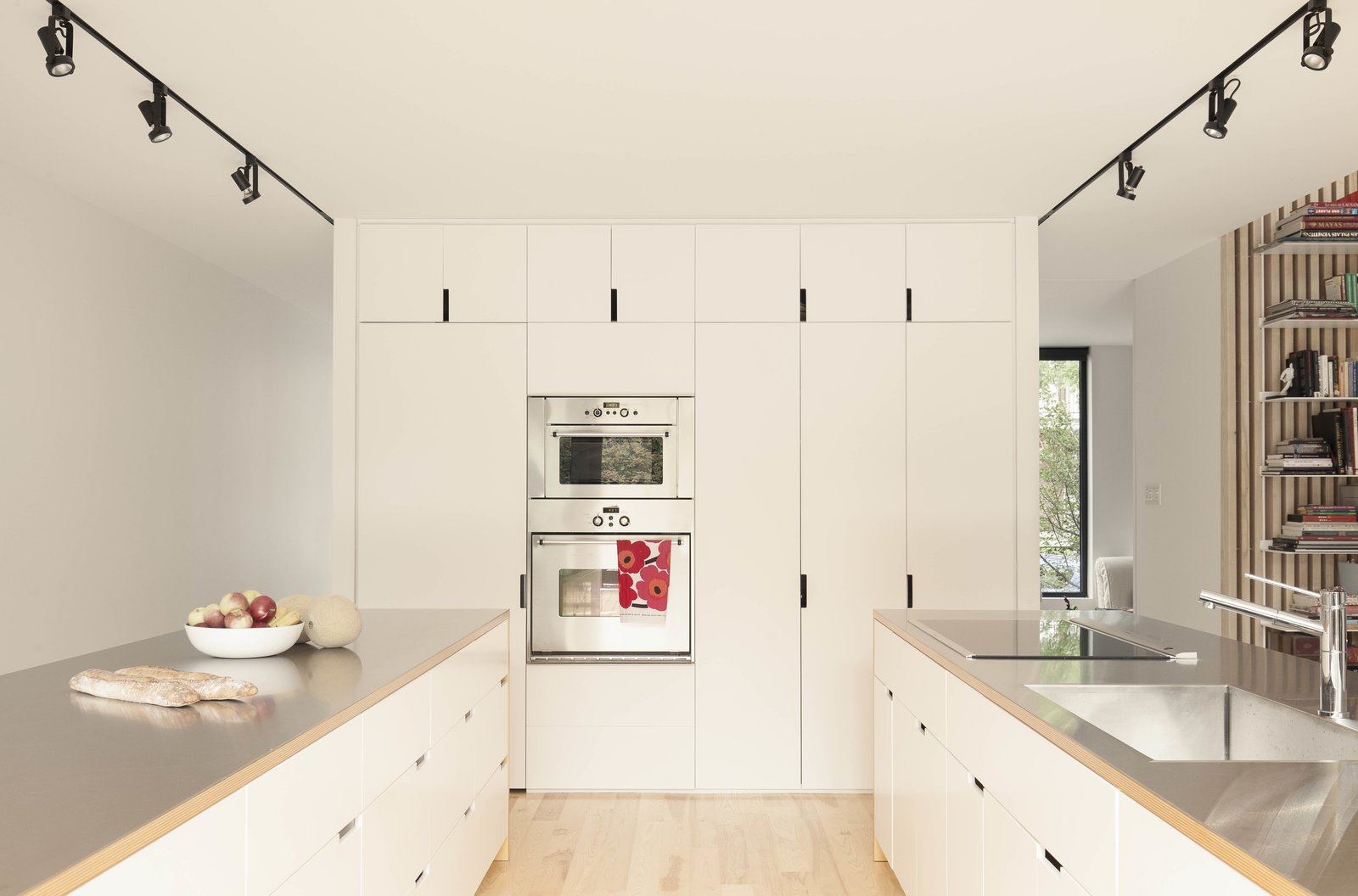 The twin kitchen islands are oriented parallel to the living room. The cabinet fronts are finished in white lacquer, with stainless-steel counters atop ash veneer.  Photo 6 of 15 in A Transformative Duplex Renovation in Montreal