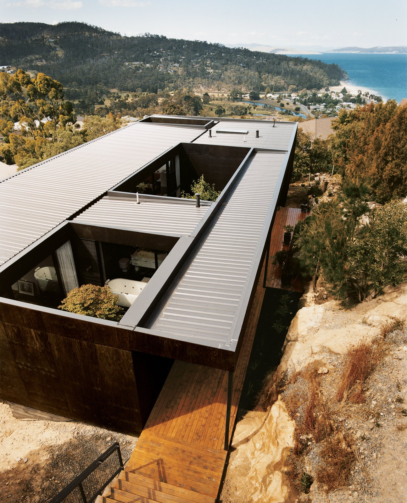 The Kingston house remains unobtrusive and well camouflaged on its hillside site despite the architects' use of modernist geometry. The outer cladding is simply plywood stained with dark Madison oil.  Photo 6 of 10 in 11 Hillside Homes That Feature a Balancing Act With Nature from Kingston Brio