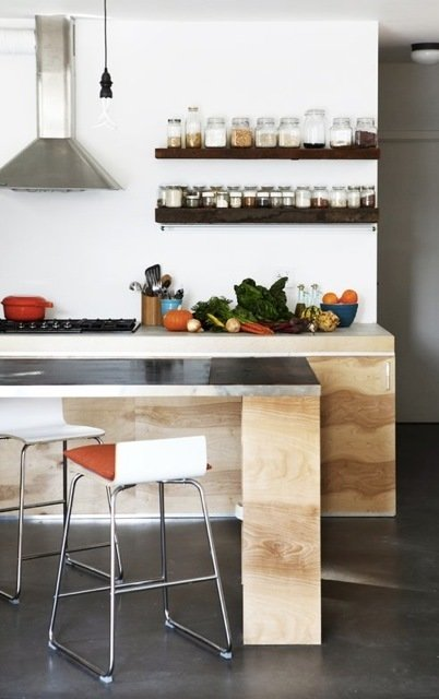 The kitchen has open storage and cabinets and an island made of plywood.  Kitchen from A Modern House on a Budget in Los Angeles