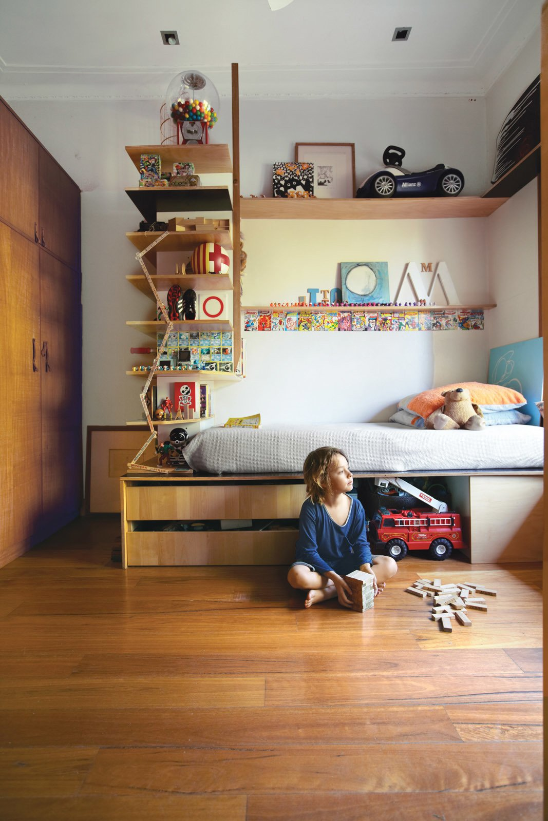 Kids Room, Bedroom Room Type, Shelves, Bed, Storage, Pre-Teen Age, Medium Hardwood Floor, and Boy Gender Tom's compact bedroom feels much larger thanks to interlocking shelves and storage. The plywood bed and surrounding shelving were custom-built by Wilkin and a hired carpenter.  Photos from Almost Perfect