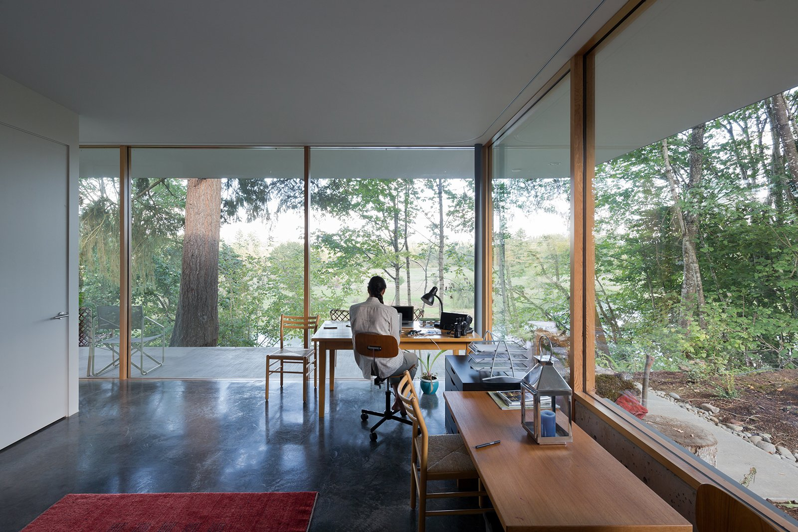 """Office, Study Room Type, Desk, Lamps, Concrete Floor, and Chair """"There are a lot of well-loved, well-used pieces that were destined for this house,"""" Andrea says of the couple's furniture collection. They placed a solid alder Homestead table from Whittier Wood Furniture in the office, which also overlooks the pond.  Indoors/Outdoors from This House Gets Better with Age"""