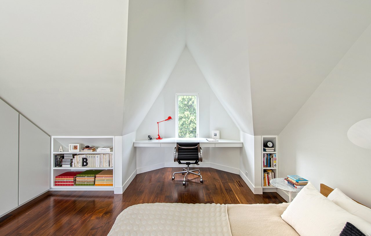 "Bedroom, Bed, Chair, Table Lighting, and Medium Hardwood Floor ""I love the master bedroom, with the geometry of the white-painted, angled roof lines and the varying shadows that this creates,"" Dubbeldam says. The naturally lit space features built-in shelves and a floating desk that overlooks the street below through a tiny window. An aluminum Eames task chair and a Serge Mouille wall light adorn the space.  studio from Modern Home Offices We Love"
