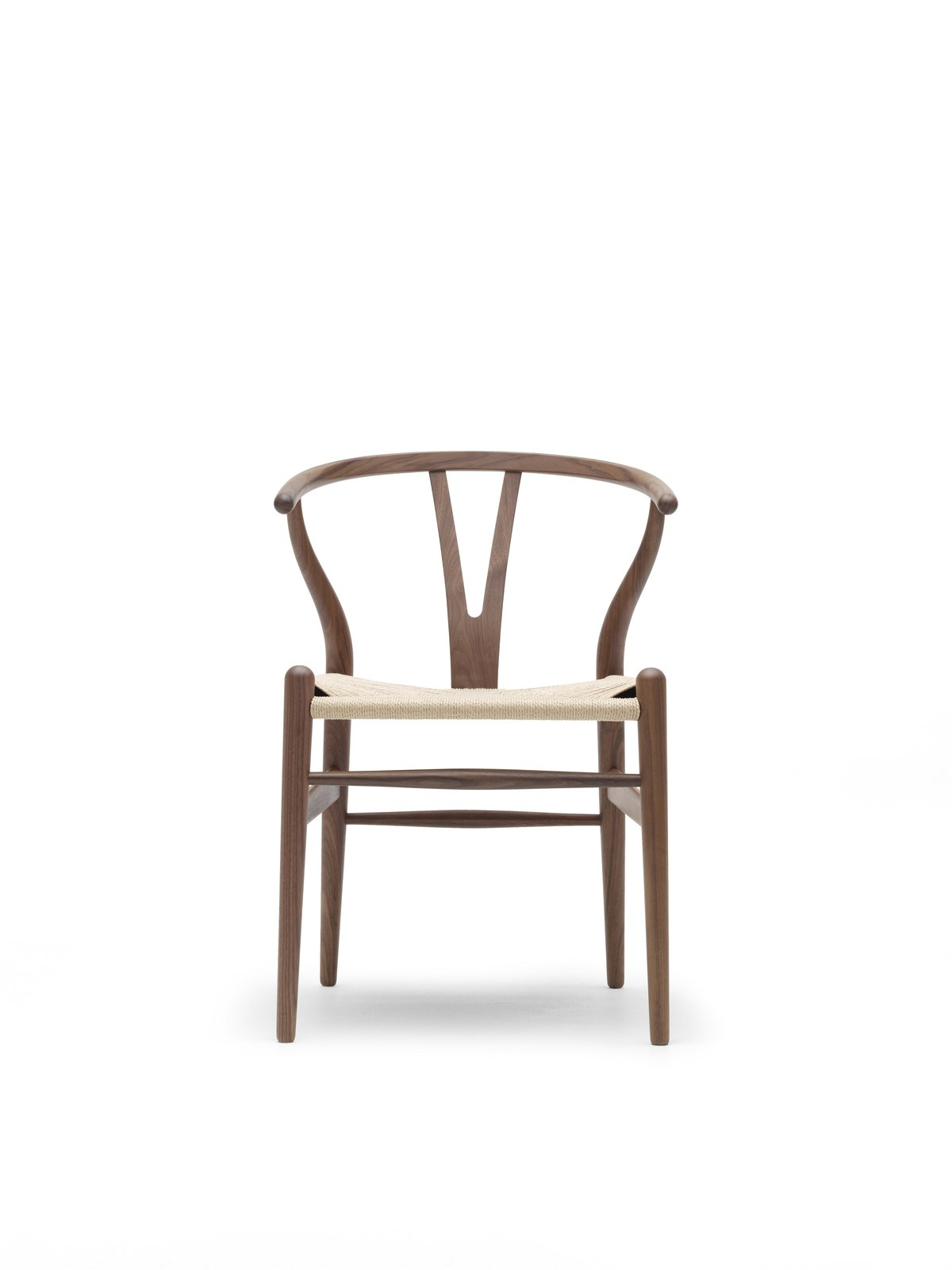 The Wishbone Chair (1949), also known as the Y Chair, marries a hand-woven seat and steam-bent frame. The chair, an undisputed modern icon, has been in continuous production since its introduction in 1950. Inspired by portraits of Danish merchants sitting in Ming chairs, this was the culmination of a series of chairs created in the '40s. Photo courtesy Carl Hansen & Son.  Photo 3 of 9 in 8 Iconic Chairs by Hans Wegner