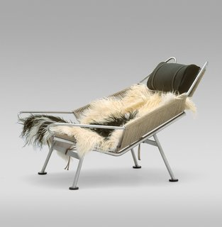 The lush design for the Flag Halyard Chair (1950) was supposedly inspired by a day at the beach, when Wegner was slowing carving himself a spot in the sand to relax. Lounging is supported by 240 meters of flag line strung through a steel frame and sheepskin covering—those coveting this chair can even reserve their own sheepskin. Manufactured by PP Møbler. Photo by Jens Mourits Sørensen.