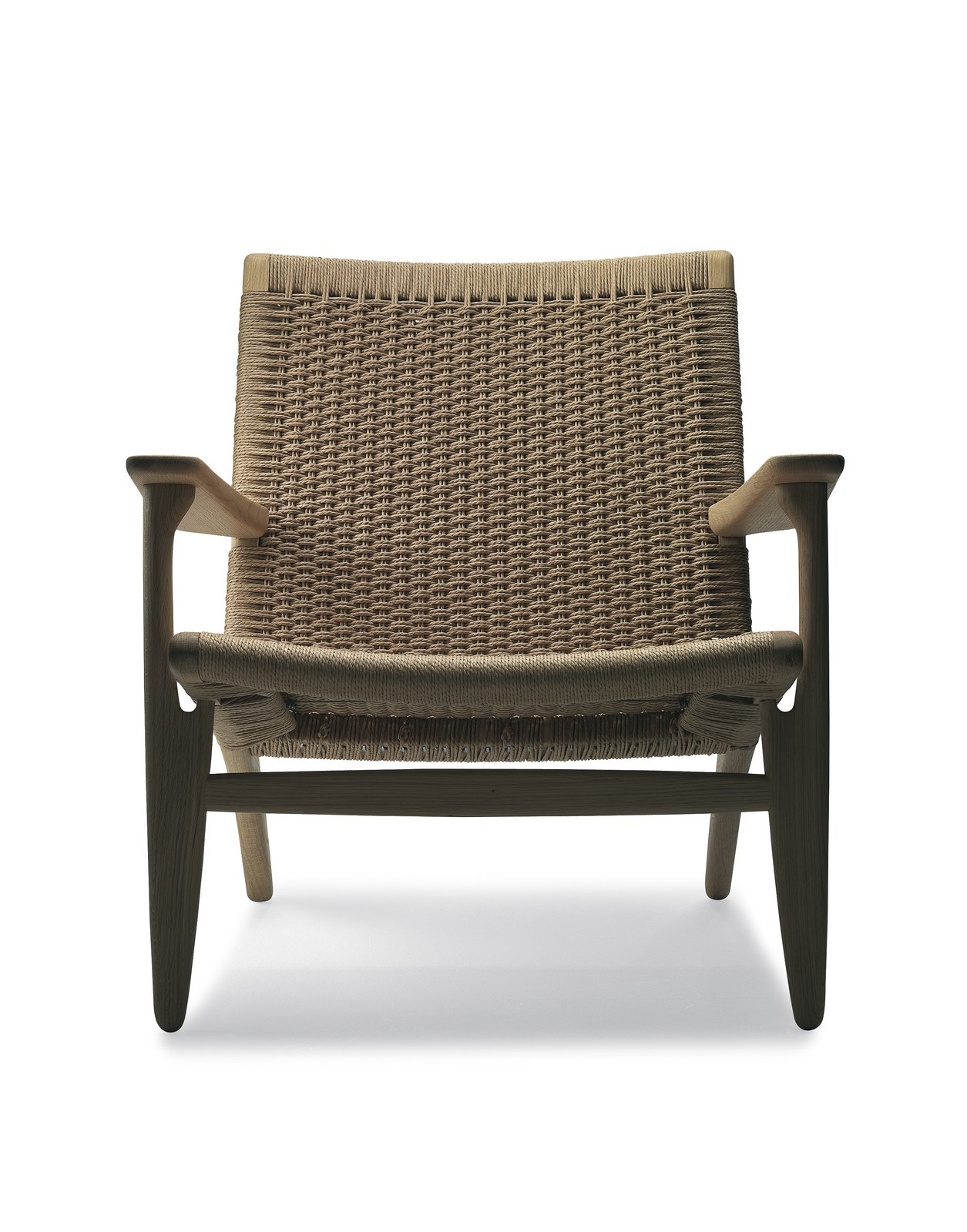 It requires roughly ten hours for a craftsman to weave paper cord across the curved frame of this oak Easy Chair (1950) before it's complete. Another example of Wegner melding design and material without unnecessary fuss or adornment. Photo courtesy Carl Hansen & Son.  Photo 9 of 9 in 8 Iconic Chairs by Hans Wegner