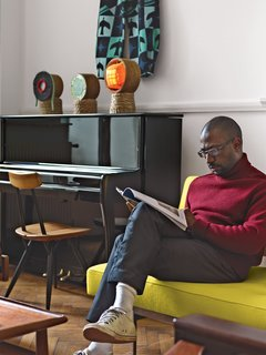 """When curating the rooms throughout their house, Udechuku and Smith mix borrowed pieces related to the temporary exhibition—such as the playful sculptural lamps crafted from found materials by Brazilian artist Rodrigo Almeida—with vintage American and European classics from their personal collection, such as a Florence Knoll sofa designed in 1954 and newly re-upholstered in a yellow Kvadrat fabric. """"We have no opening hours but people call or knock and—if we are home—we welcome them in and put the kettle on."""" —Ike Udechuku"""