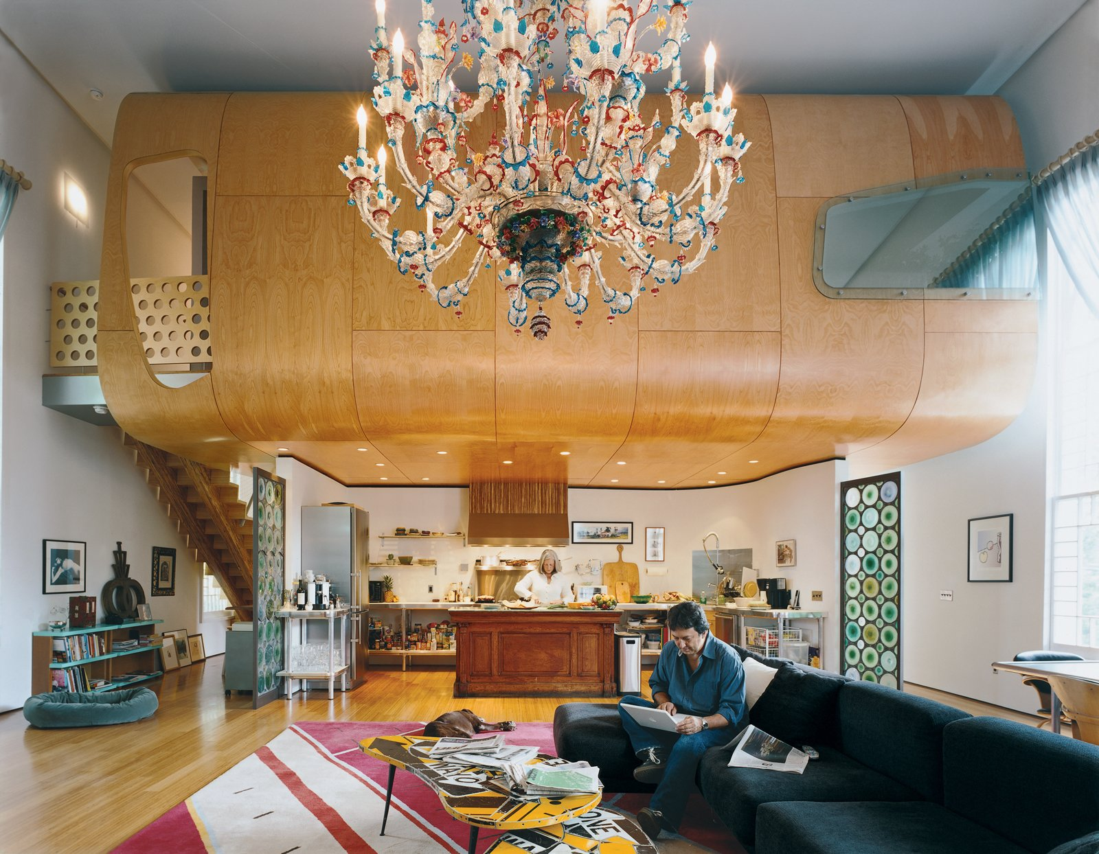 With the free-floating birch pod defining the space, and the massive Venetian chandelier accentuating the volume, the great room is, indeed, great. The Suarezes wanted the living area to be a place where the family could be occupied individually while still together. Bonnie works in the kitchen while Santiago (seated on an IKEA couch borrowed from one of their sons until they find something else) works on the computer.  Heavenly Converted Churches by William Harrison from At Home in a Modern Church