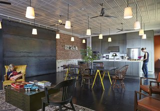 In Auburn, Alabama, architect David Hill purchased a historic brick building that had served as a Baptist church, pool hall, and barbershop. When renovating the space's interior, Hill made an effort to retain its large, open spaces, and carefully restored the original metal ceiling tiles.