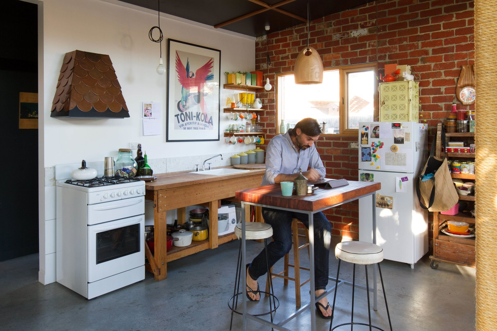"""Kitchen, Wood Counter, Wood Cabinet, Pendant Lighting, and Concrete Floor Fuscaldo and Krien found an old workbench and used the wood to create the counter around the kitchen sink. Photo by Nic Granleese.  Search """"glass house australia's sunshine coast"""" from An Australian Architect's Simple Brick House With Impressive Green Roof"""