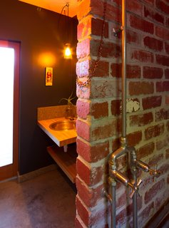 """Salvaged bricks were used inside and outside the house. Krien describes the lone bathroom as """"half nightclub, half swimming pool change room,"""" and says it is her favorite space in the house. Photo by Nic Granleese."""
