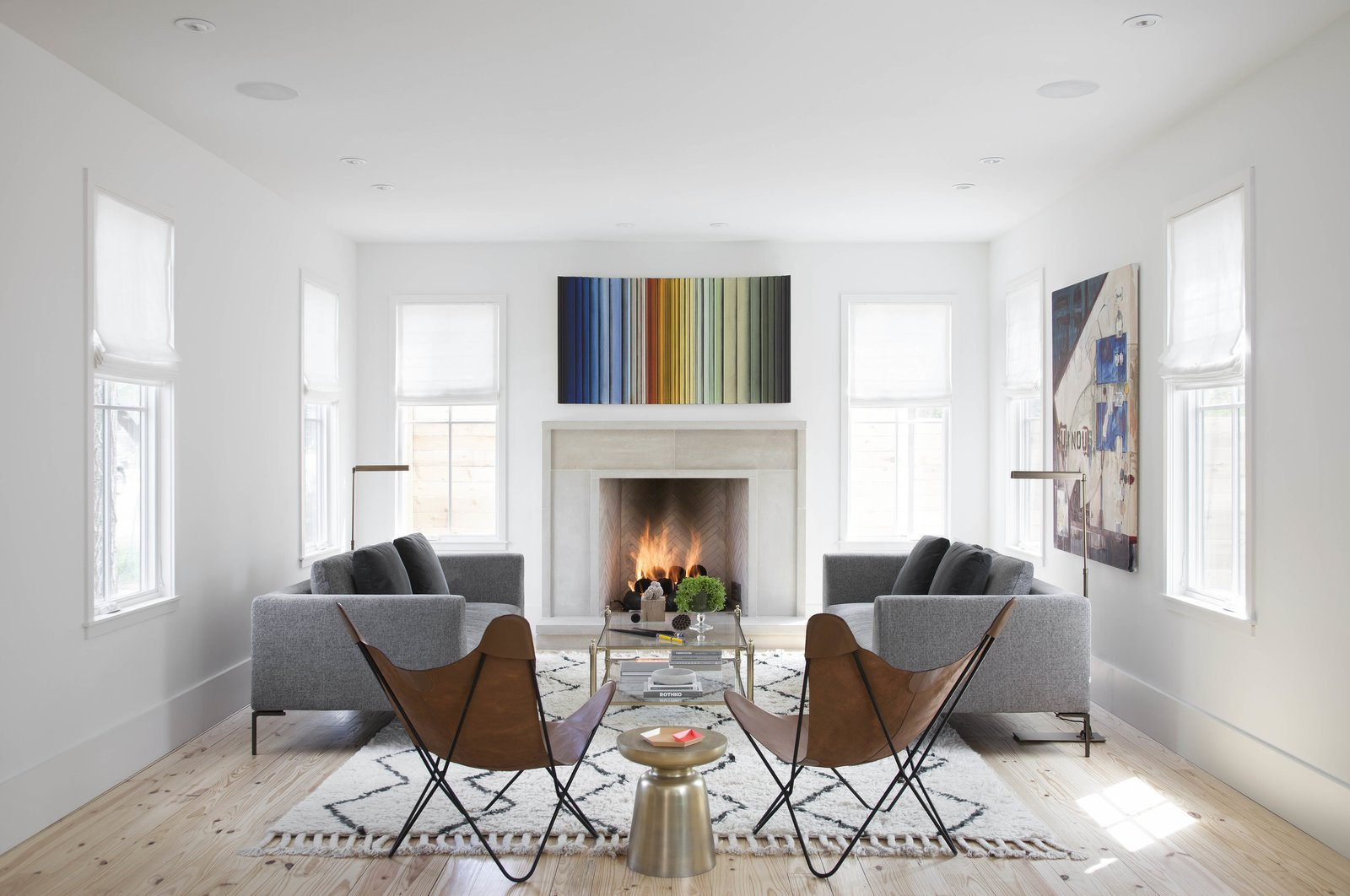 "Living Room, Wood Burning Fireplace, Light Hardwood Floor, Chair, Sofa, Rug Floor, and Coffee Tables Additions of color in the interior are minimal, but when they are included, they make a lasting impact, such as with this rainbow art piece by local artist Roi James. ""Although we had commissioned the piece based on a recent show we went to, I don't think either of us realized that it would work so well with our [colorful] cookbook display [in the dining area],"" Flournoy admitted. The rug and brass side table are from West Elm, the couches from Scott+Cooner. The butterfly chairs were custom made by Robert Smith.  Photo 6 of 8 in Modern Take on a Texas Farmhouse"