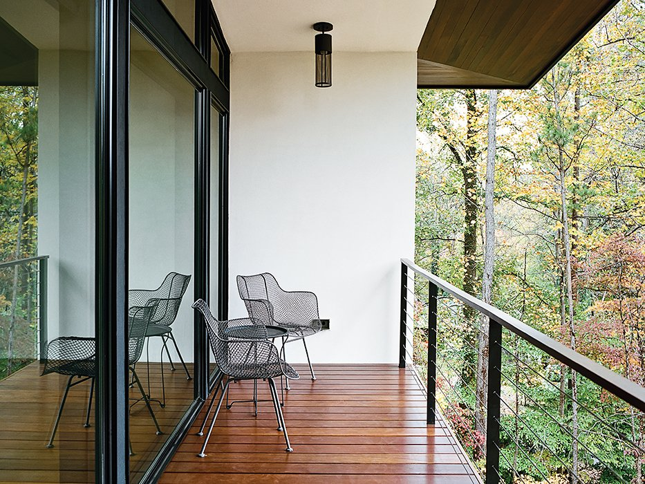 Outdoor, Small Patio, Porch, Deck, and Wood Patio, Porch, Deck Wire chairs by Rejuvenation and pendants by Hinkley Lighting grace the balcony outside.  Photo 12 of 13 in Minimal North Carolina Home Built for a Tech-Forward West Coast Couple