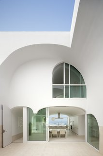 """Dramatic arches characterize this enigmatic California beach house that's elevated six feet above the sand to guard from major storms. Called the Vault House, it was designed by architecture firm Johnston Marklee. As principal Mark Lee explains: """"The envelope was so strict that the design process was more subtractive than additive; we carved away a solid mass to create the rooms. We were reluctant to broadcast the content right away, preferring to mask the complexity and reveal it a little at a time."""""""