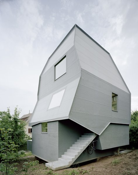 A playful twist on the concept of a pitched roof, the Just K house designed by AMUNT in Tubingen, Germany, features a monochromatic, blue-gray facade with strikingly skewed geometric forms. An exterior staircase leads to a separate entrance at the rear of the building, allowing the structure to be used as two separate units.